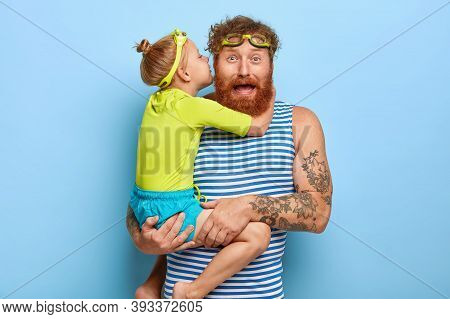 Photo Of Funny Ginger Father Receives Hug And Kiss From Small Daughter, Carries Child On Hands, Wear
