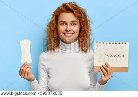 Female Hygiene Concept. Redhead Smiling Woman Holds Clean Period Sanitary Napkin Pad And Menstruatio