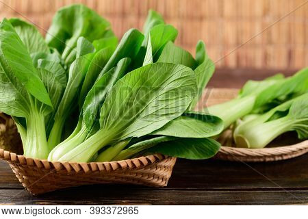 Fresh Bok Choy Or Pak Choi(chinese Cabbage) In Bamboo Basket On Wooden Background, Organic Vegetable