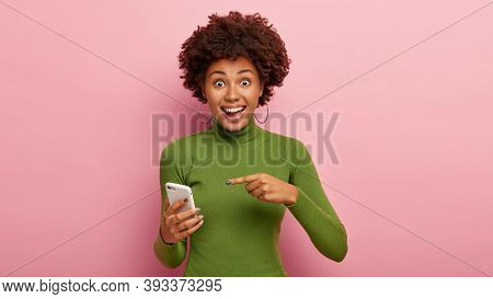 Just Look At My Electronic Device. Cheerful Beautiful African American Woman Points At Mobile Phone,