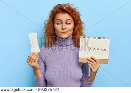 Women, Fertility, Hygiene Concept. Young Redhead Woman Holds Clean Sanitary Napkin And Periods Calen