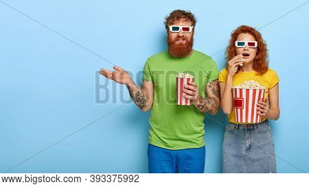 Thrilled Couple Gaze With Great Impression At Camera, Watch Exciting Movie In Cinema, Grab Popcorn,