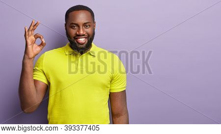 Waist Up Shot Of Cheerful Black Young Man Makes Okay Gesture With One Hand, Smiles Broadly, Gives Ap
