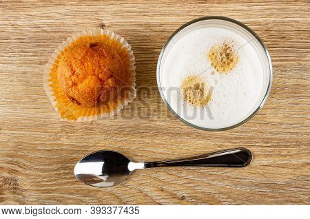 Orange Muffin On Paper, Transparent Glass With Latte-macchiato, Teaspoon On Wooden Table. Top View
