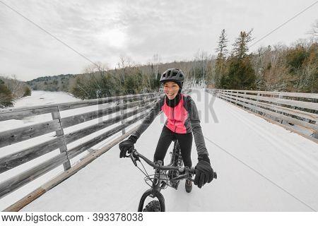 Winter bike sport fun happy cyclist Asian girl cycling on snow bridge with fat e-bike. Electric biking.