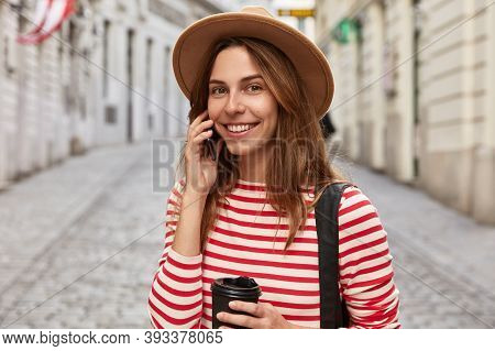 Cheerful Female Tourist Poses In Urban Background, Drinks Takeaway Coffee In Paper Cup, Has Telephon