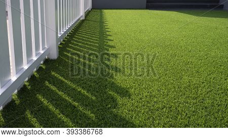 Sunlight And Shadow Of White Wooden Fence On Green Artificial Turf Surface In Front Yard Of Home, Se