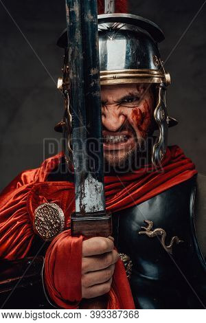 Savage Roman Barbarian With Blood On His Face Looks At Camera Holding His Sword With Angry Face In D