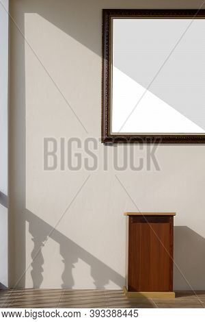 Sunlight And Shadow On Surface Of Vintage Photo Frame On Mastic Yellow Cement Wall With Wooden Stand