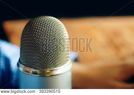 Photo Of A Professional Vintage Microphone For Broadcast. Podcast Studio With A Person In The Backgr