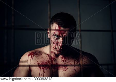 Halloween Concept. Aggressive Person. Strong Aggressive Monster Behind Grid. Bodybuilder Nude Torso