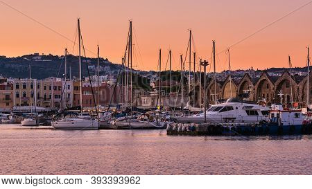 Sunrise Over Old Venetian Harbour Of Chania, Crete, Greece. Sailing Boats Anchored By Pier, Old Vene