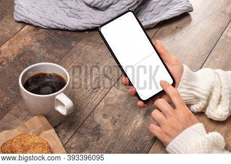 Mockup Image Of Woman's Hands Holding White Mobile Phone With Blank Screen On Vintage Wooden Table B