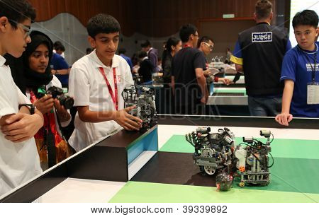SUBANG JAYA - NOV 10: Unidentified students watch their robots with programmed response compete in a football match at the World Robot Olympaid on November 10, 2012 in Subang Jaya, Malaysia.
