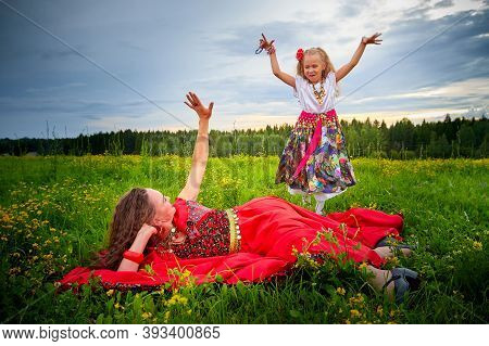 Mother And Daughter In Colorful Gypsy Dresses Resting And Having Fun In Meadow With Green Grass. Lit