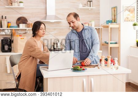 Couple Preparing Healthy Salad In Kitchen Reading Online Recipe. Man Helping Woman To Prepare Health