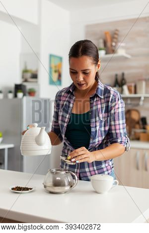 Housewife Preparing Hot Drinkg In Kitchen Using Aromatic Herbs On Teapot. Woman, Lifestylem, Beverag