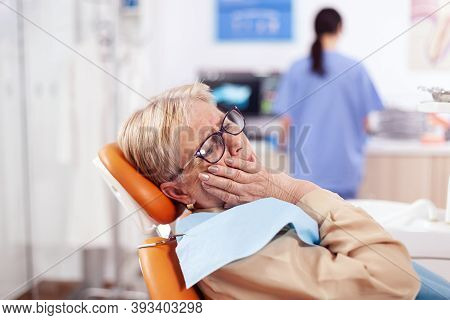 Elderly Patient Waiting Diagnostic From Dentist Doctor Sitting On Dental Clinic Chair. Senior Woman