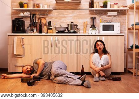 Traumatised Wife Smoking And Crying Sitting On The Floor. Abused Terrified Beaten Woman Covered In B
