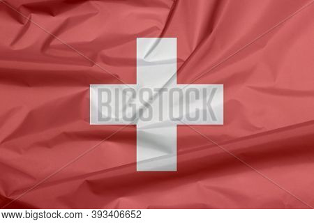 Fabric Flag Of Switzerland. Crease Of Swiss Flag Background, It Is Consists Of A Red Flag With A Whi