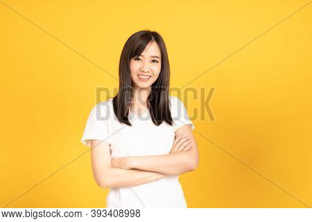 Happy Asian Young Woman Wearing White T-shirt Standing With Crossed Arms Ready To Shoot At Studio) S