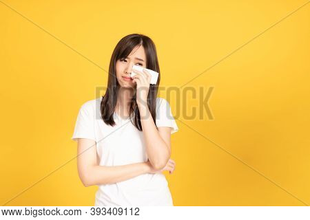 Asian Young Woman Wearing White T-shirt Standing And Holding A Tissue Paper Using Her Face Wiping Te