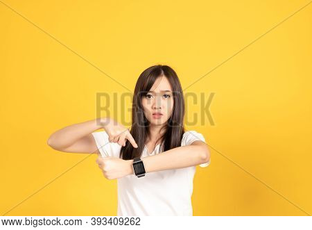 Asian Young Woman Wearing White T-shirt Standing. She Looking On Smart Watch On Hand Put Hand On Che