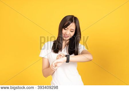 Asian Young Woman Wearing White T-shirt Standing And Looking At Her Smartwatch  At Studio Shot On Ye