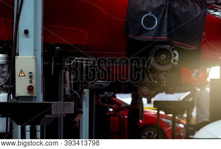 Selective Focus On Lift In Auto Repair Shop. Red Suv Car Lifted In The Garage For Repair And Mainten