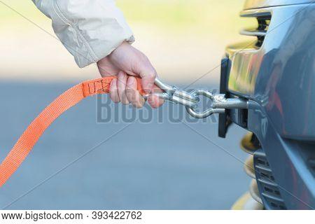 Woman assembling towing line to a broken car