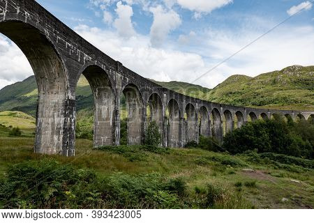 The Scottish Landscape With Famous Glenfinnan Viaduct In Scotland From Bottom With The Blue Sky And