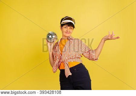 Dancing With Discoball. Portrait Of Senior Woman In Stylish Outfit Isolated On Yellow Studio Backgro