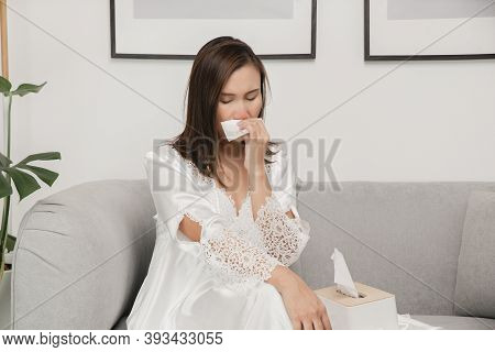 Symptoms Of Allergic Rhinitis In Women. Sick Woman In White Nightwear With A Cold Blowing Her Nose I
