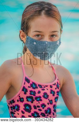 Girl Child In A Medical Mask And Swimsuit Near The Pool, The Concept Of Rest And Vacation During The