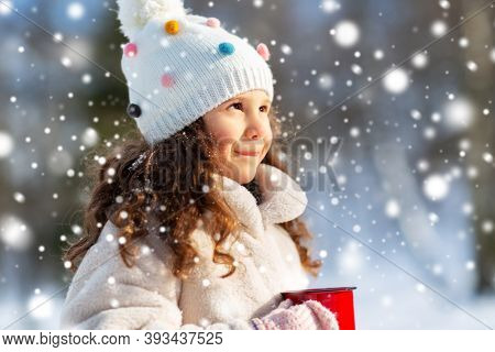 childhood, christmas and season concept - happy little girl with cup of hot tea in winter park over snow