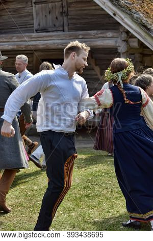 Latvian Culture Tradition. Midsummer In Latvia.. Folk Dance Group In Latvian Traditional Costume.