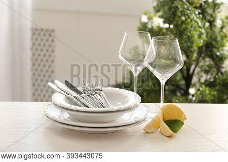 Set Of Clean Dinnerware And Lemon On Table Indoors