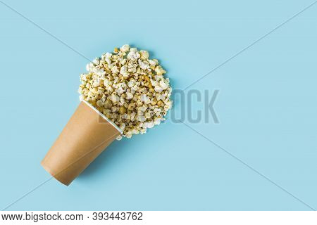Fresh Popcorn Scattered From Paper Box On Blue Background. Cinema Snack Concept. Food For Watching M