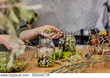 Woman Prepares Fermented Olives In Glass Jars In The Kitchen. Autumn Vegetables Canning. Healthy Hom