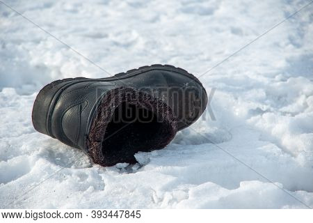 Christmastide. Old Worn Rustic Boot Thrown On White Snow Indicates Where The Bride Or Groom Will App