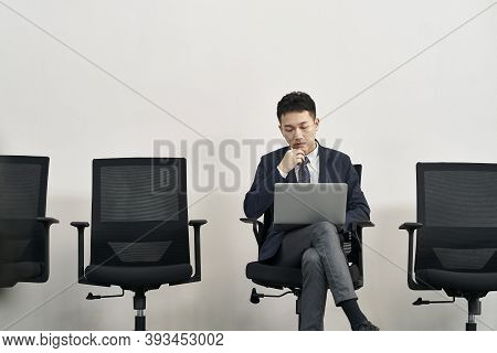 Young Asian Job Seeker Sitting In Chair Preparing For Interview Using Laptop Computer While Waiting