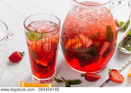 Closeup On Glass And Jug Of Fresh And Cool Red Strawberry Lemonade With Mint And Orange