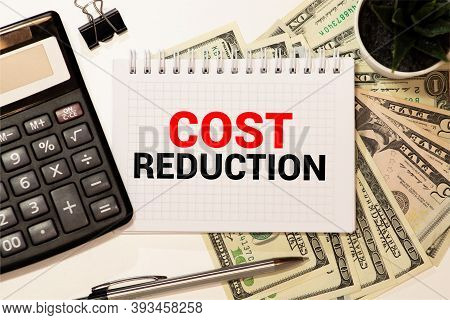Cost Reductions Words On Copybook Page, Production Or Reselling Business Concept For Reduction Expen
