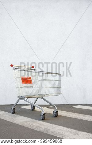 Empty Shopping Cart Trolley Stands Near Mall With Copy Space. Grocery Cart On The White Wall Store.