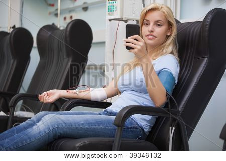 Blonde woman relaxing in a chair while getting dialysis n hospital