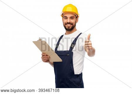 profession, construction and building - happy smiling male worker or builder in helmet with clipboard showing thumbs up over white background