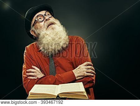 An intelligent old man with a long gray beard reads an old book and looks up as a sign of insight. Old age wisdom. An old scientist makes a great discovery.