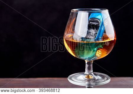 Composition With Miniature Car In A Glass Of Whiskey. Drive Drunk Concept. Isolated On Black Backgro