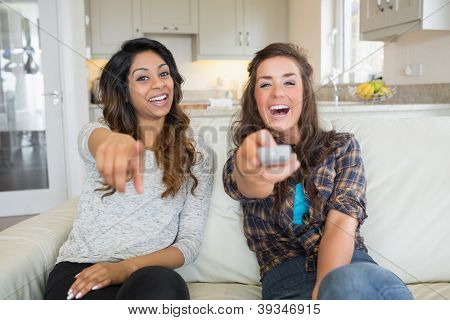Two women smiling and laughing at television holding a remote on sofa