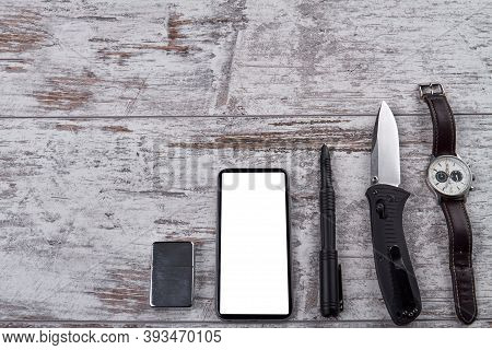 Smartphone With White Screen For Copyspace. Set Of Handy Tools For A Hike. White Wooden Rustic Backg